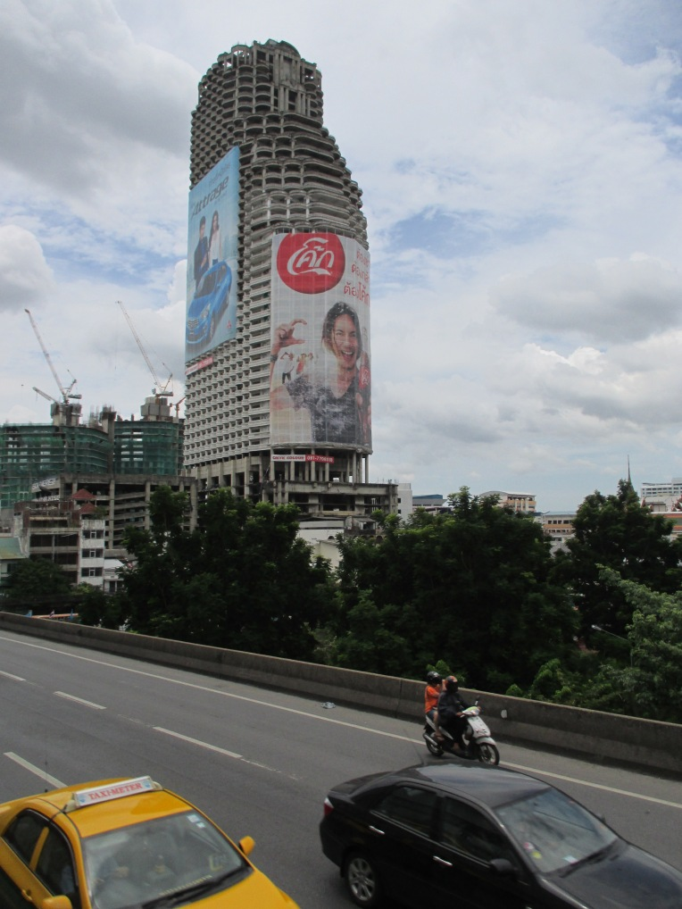 A tall abandoned apartment at Saphan Taksin is now used as a billboard.