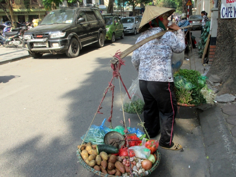 A woman delivers vegetables to eating houses early in the morning.