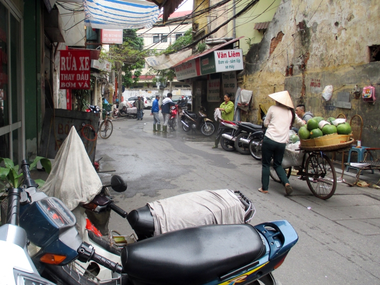 A motorcycle-wash is set up on a quiet street.