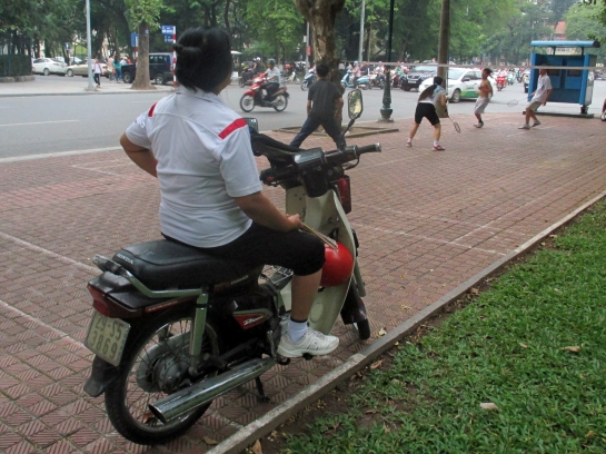 A motorcyclist pauses to watch a good game of badminton in the city centre.
